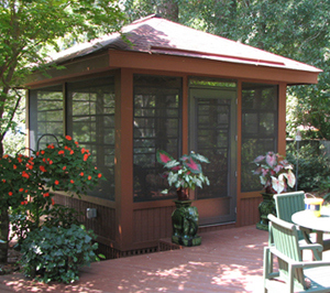 detached screen porch with flowers all around