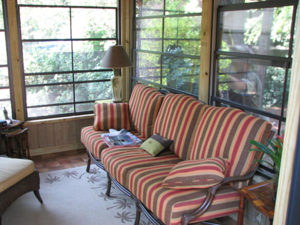 inside of screen porch with striped sofa