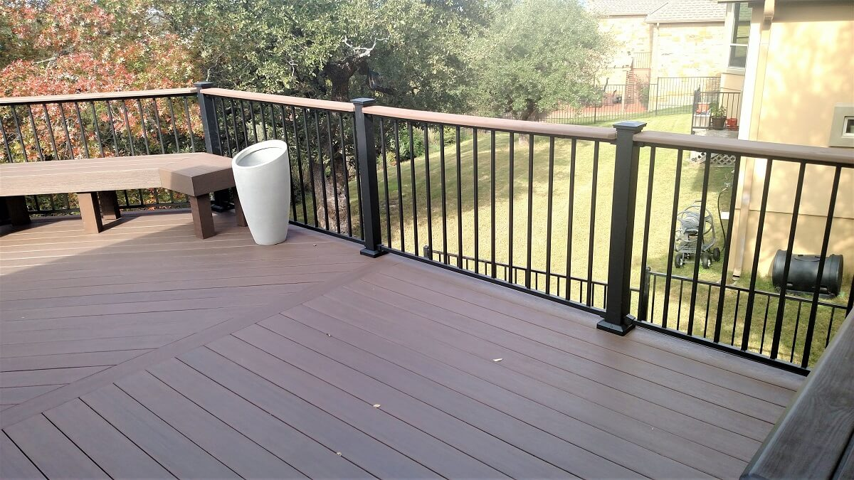 Backyard wood deck with railing and floating bench