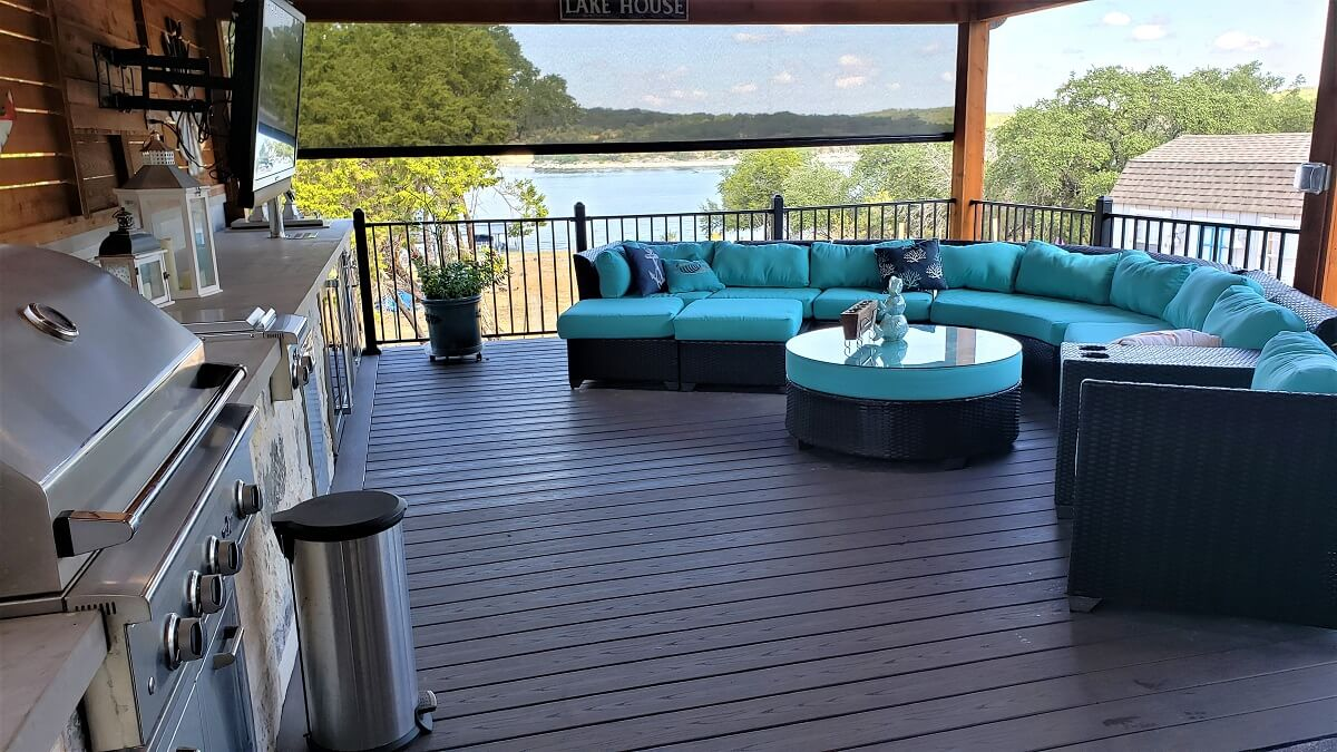 Covered deck with outdoor kitchen and seating area overlooking water