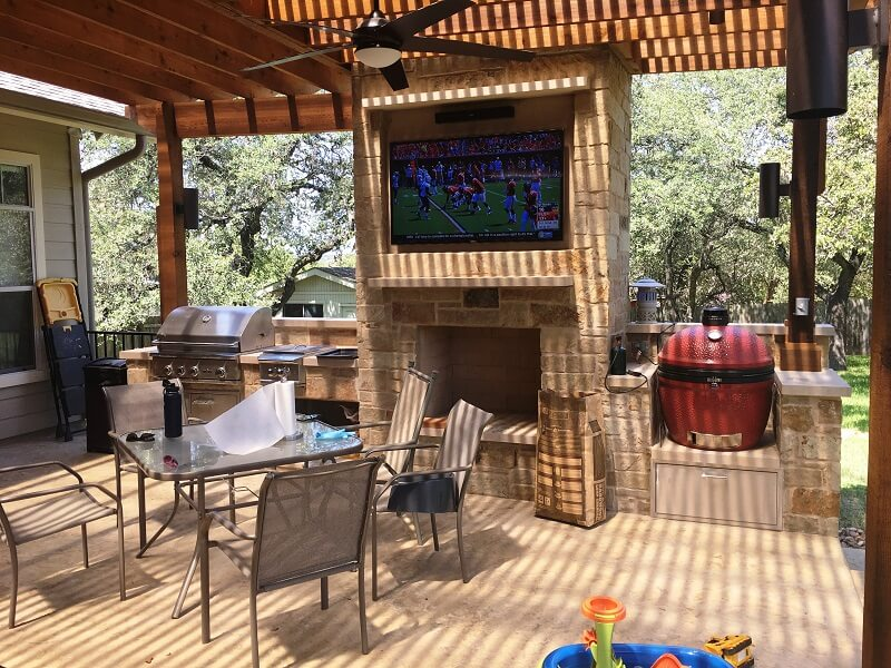 Outdoor fireplace with flat TV on top