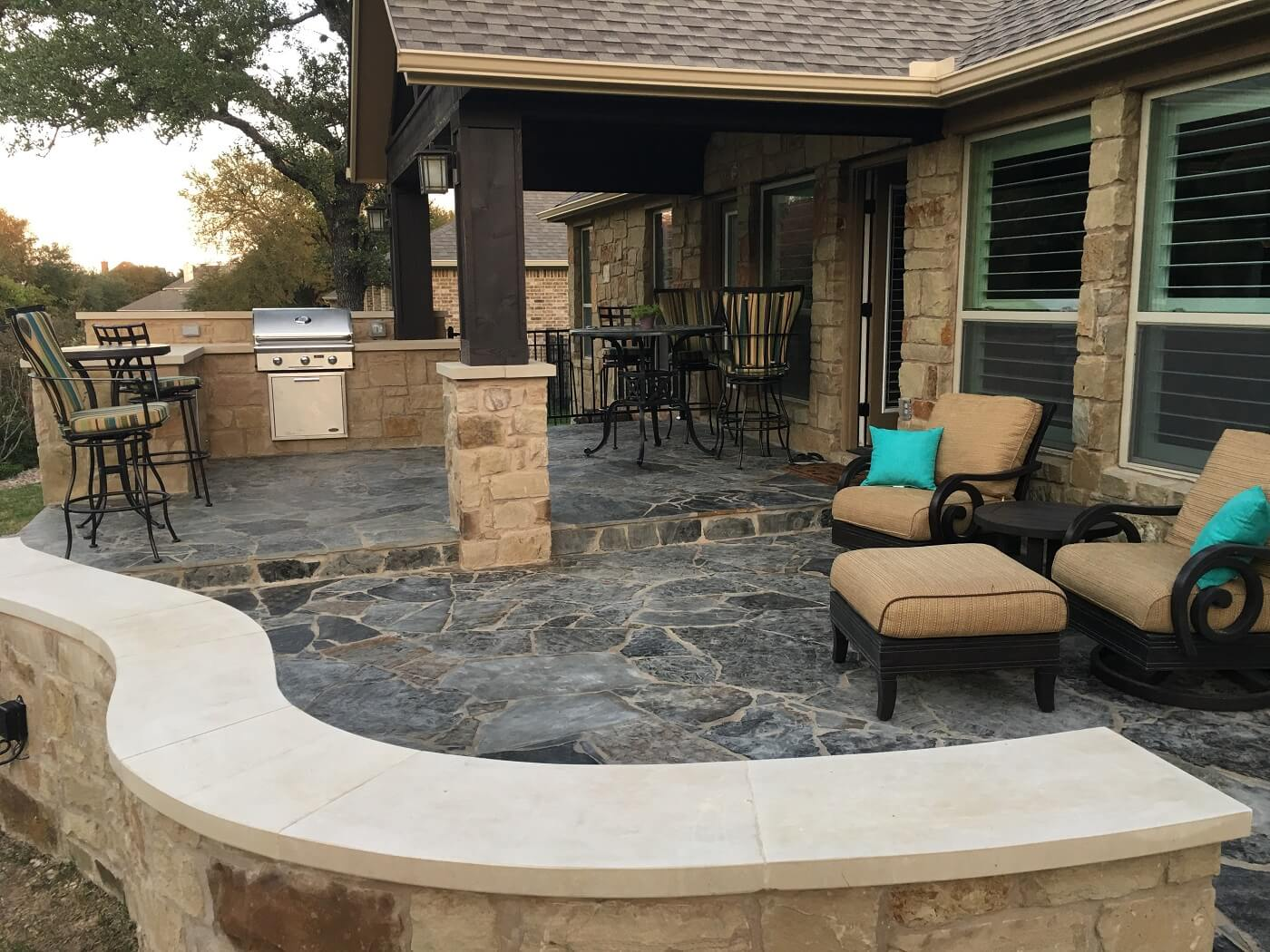 Covered and open patio with outdoor kitchen and seating area