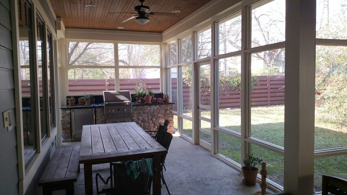 Backyard screened porch with outdoor kitchen and dining area