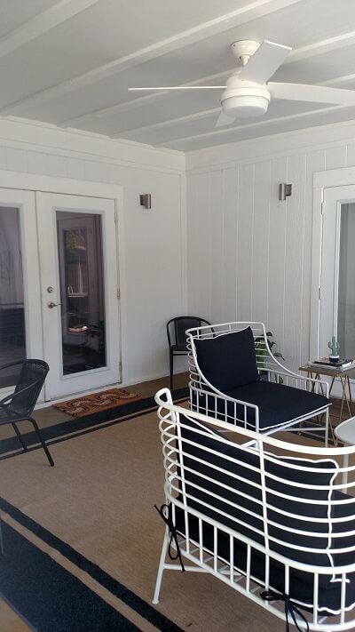 Inside of screened porch with seating area and ceiling fan