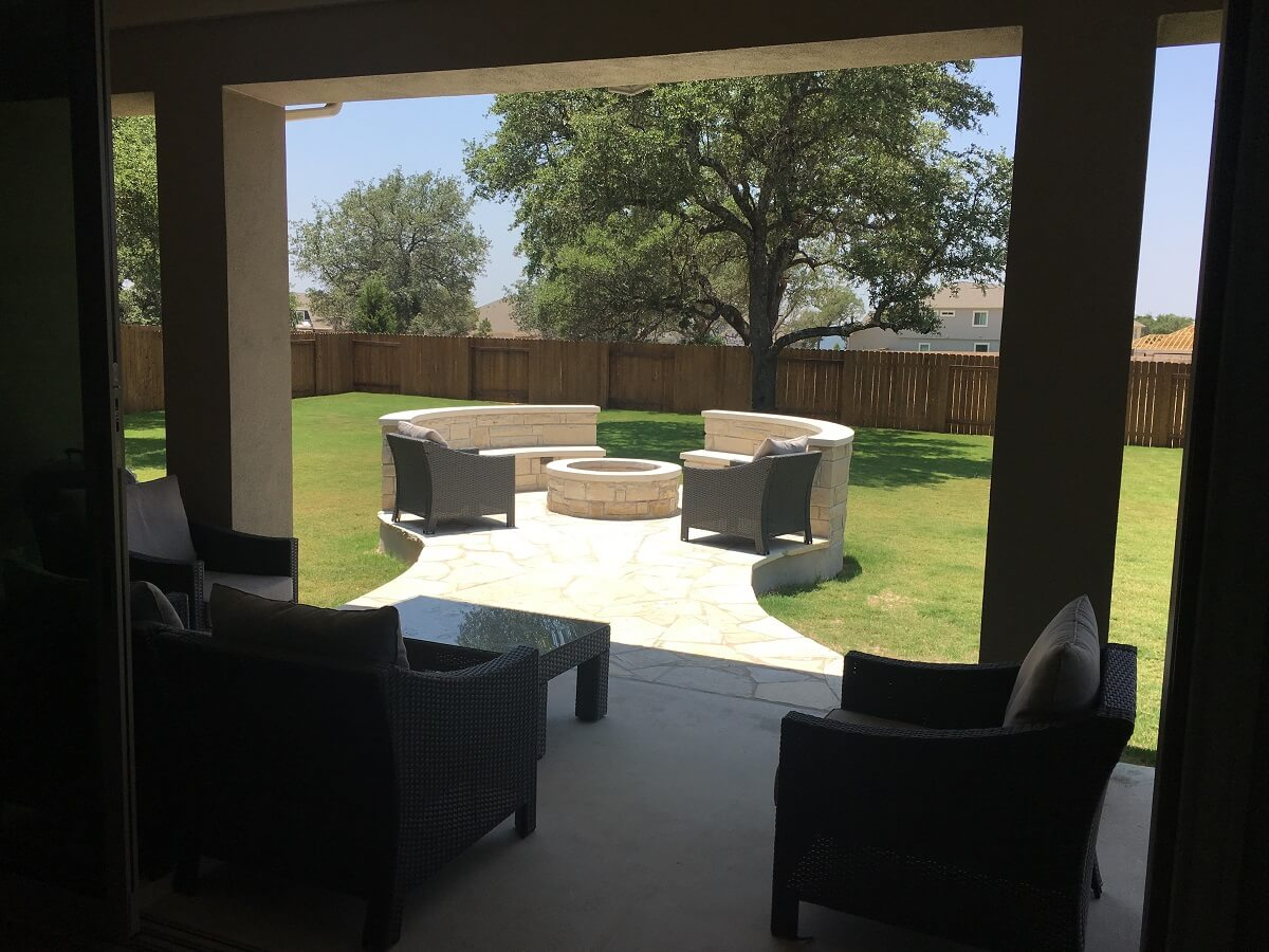 Inside home view of patio with fire pit and seat wall