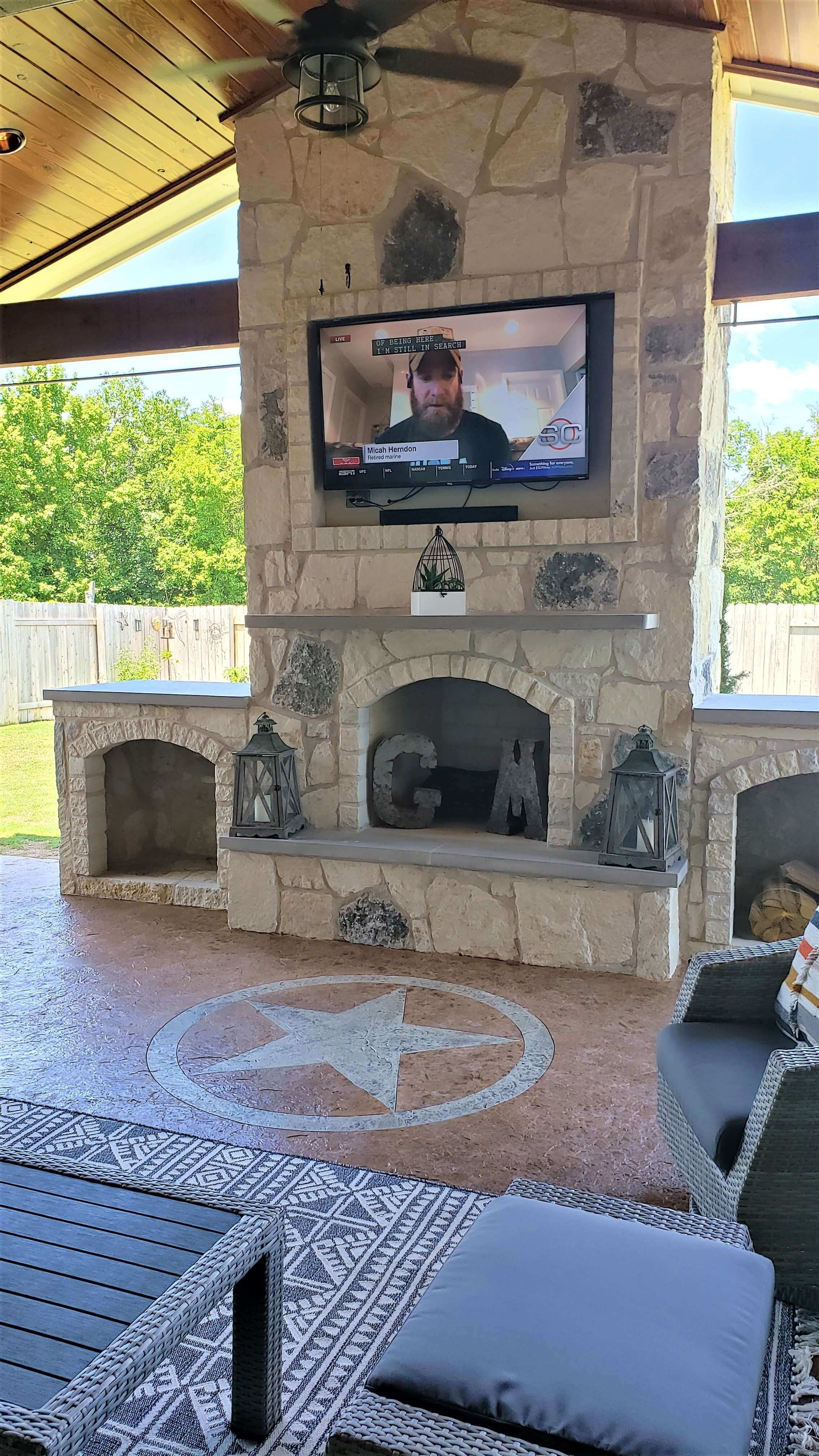 Custom outdoor fireplace with mounted flat TV