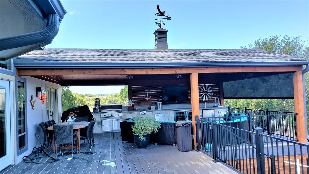 -Covered deck and patio with outdoor kitchen and dining area