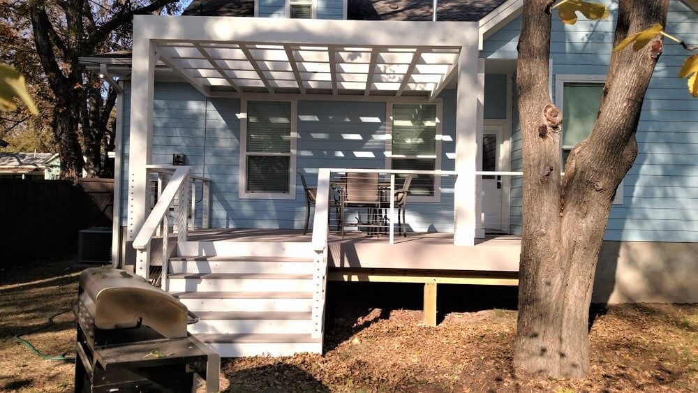 Backyard deck with white pergola and seating area