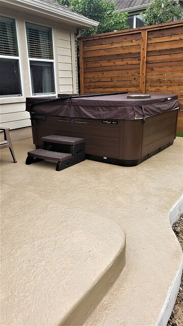 Custom hot tub on patio with privacy wall