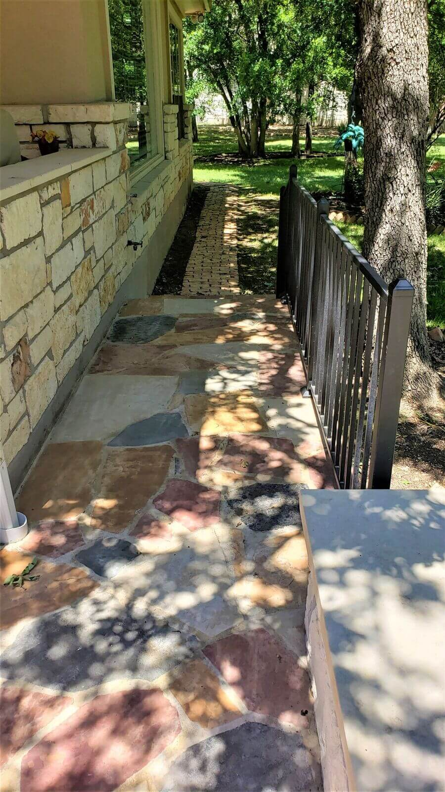 Extended side yard area of flagstone patio with railing
