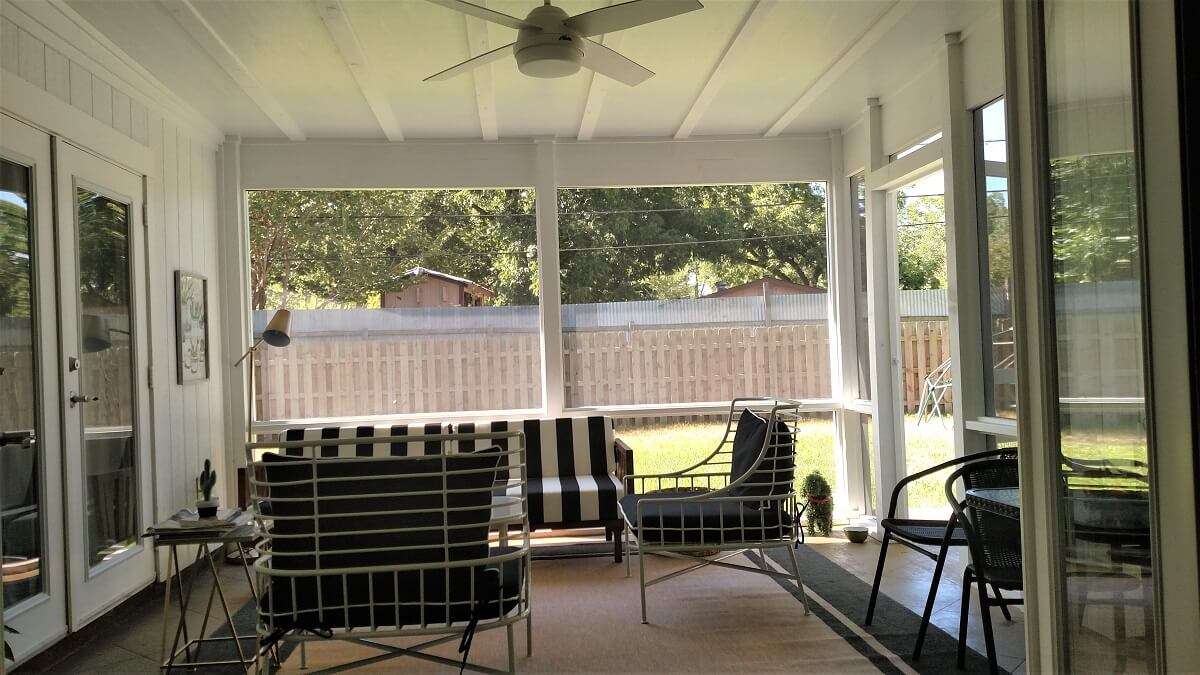 Inside view of screened porch with seating area