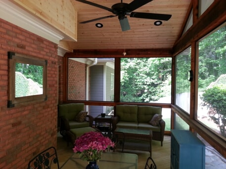 screened porch with sitting area and flowers on the table
