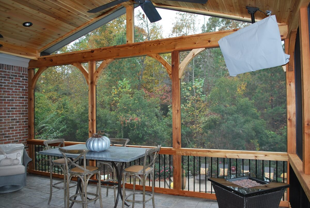 Interior of screened porch with dining area and silver pumpkin decor on table