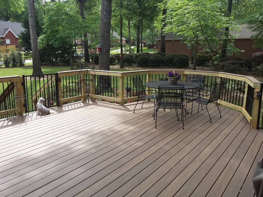 Backyard wood deck with seating area and dog seating near deck gate