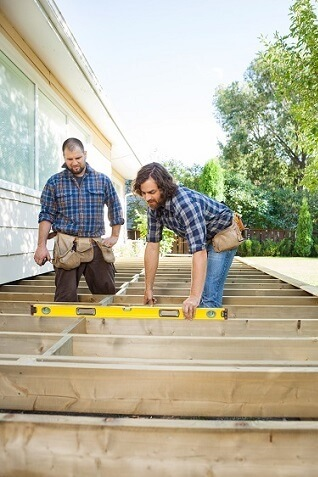 Workers measuring wood for deck