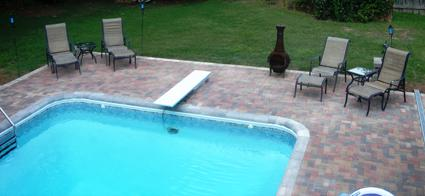 Paver patio around a pool with a diving board