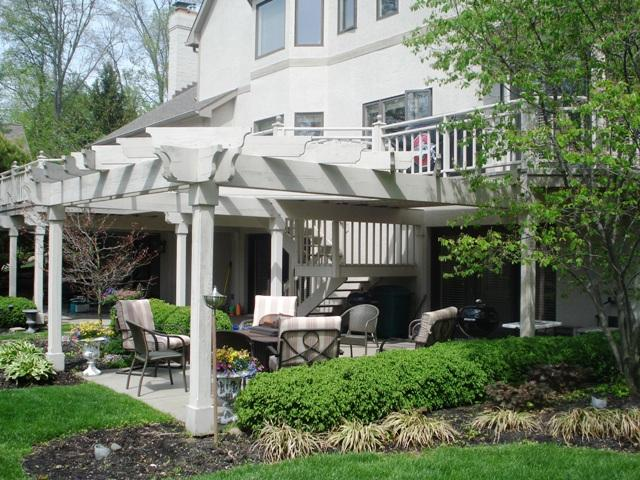 White pergola with deck and patio furniture