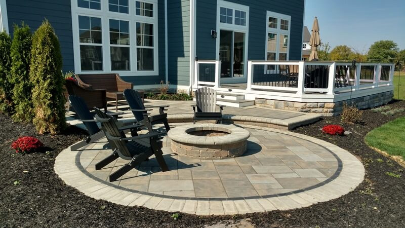 Custom backyard patio and deck with fire pit