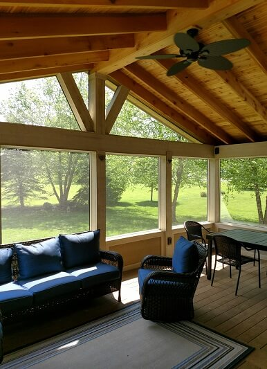 Seating area on screened porch with backyard view