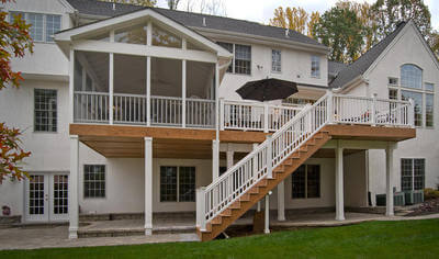 Custom backyard deck and screened porch with white railing