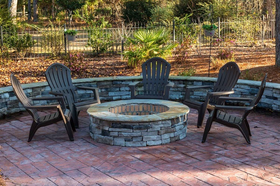 Custom backyard patio with fire pit and seat wall