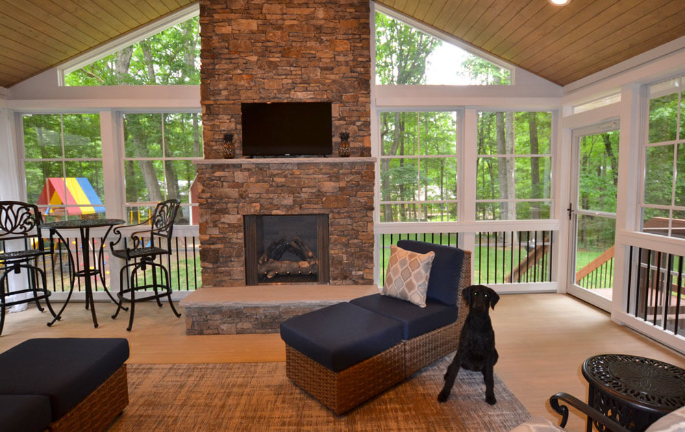 Screened porch with outdoor fireplace and black dog