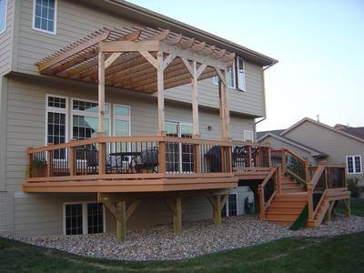 Attached wood pergola follows shape of deck