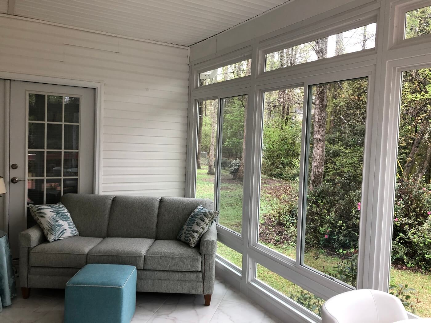 Couch on sunroom with backyard view