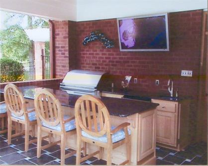 This covered patio space features an outdoor kitchen with bar seating along with a wall mounted TV
