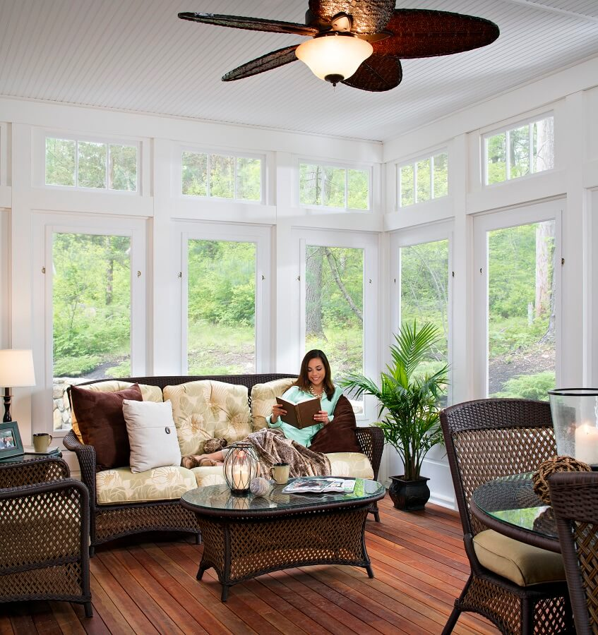 woman sitting in her sunroom with large windows