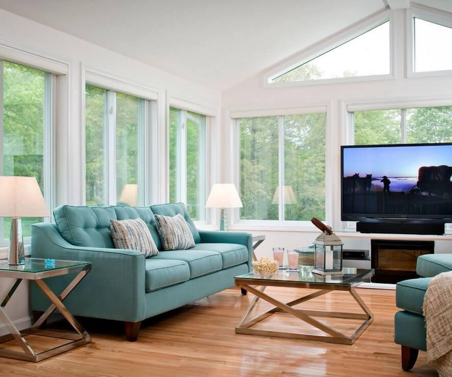 sunroom with green couch, large windows and TV
