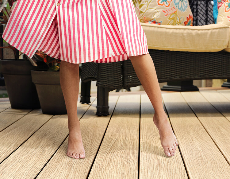 Woman standing barefoot on a deck, in a red and white striped skirt