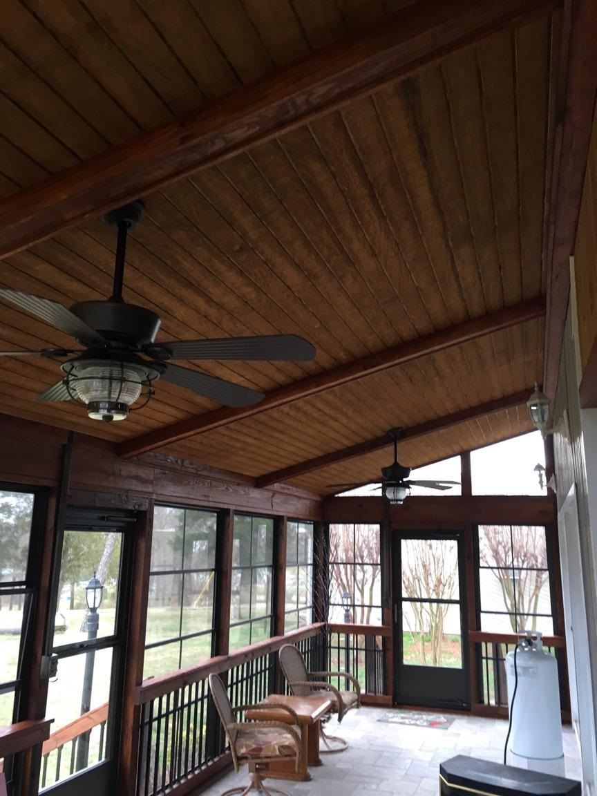enclosed patio with ceiling fans and slanted wood ceilings