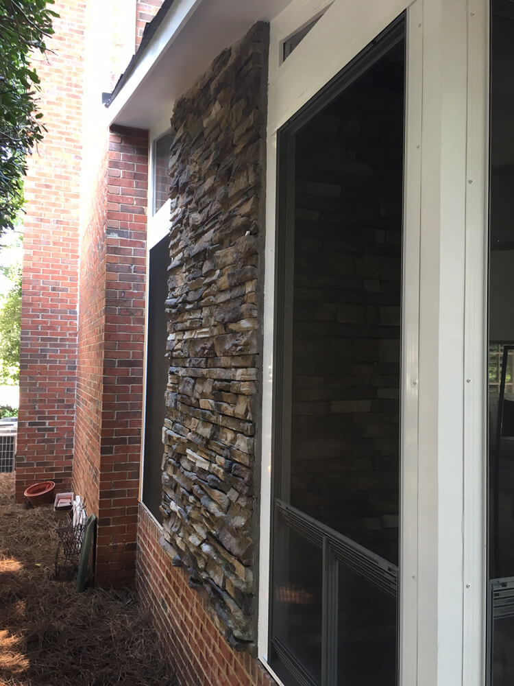 Custom porch with stone facade on outdoor fireplace