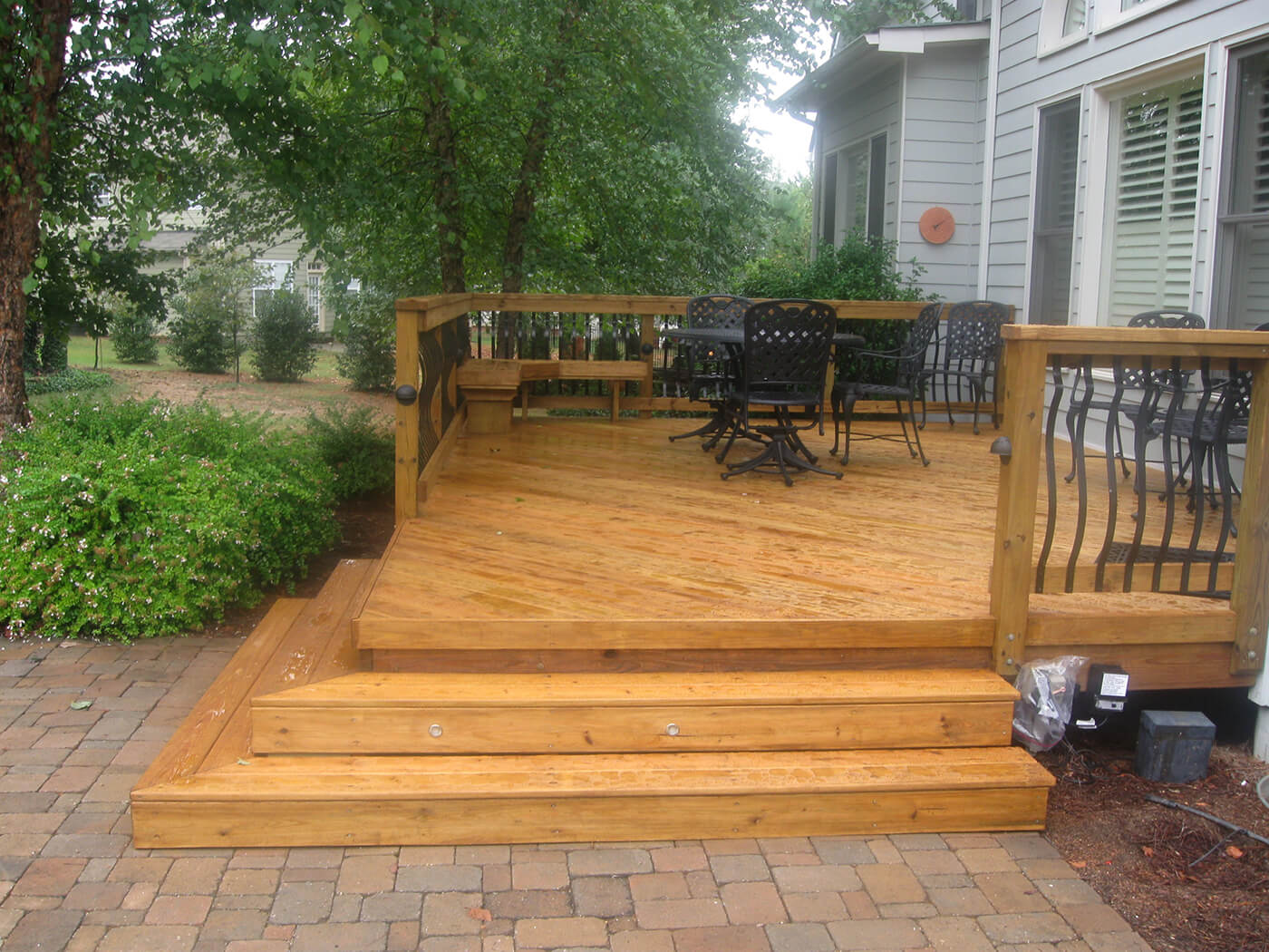 Custom backyard wood deck with railing and floating bench