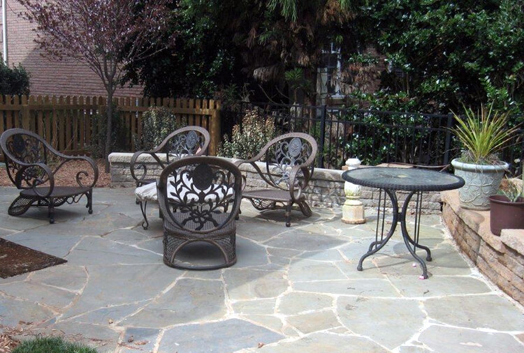 bluestone flagstone patio with a seating wall and outdoor furniture