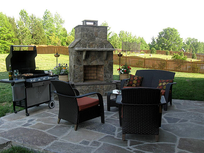 outdoor patio fireplace next to barbecue and outdoor furniture