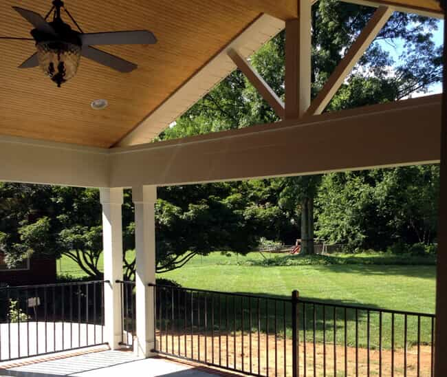 covered porch with vaulted ceiling and railing