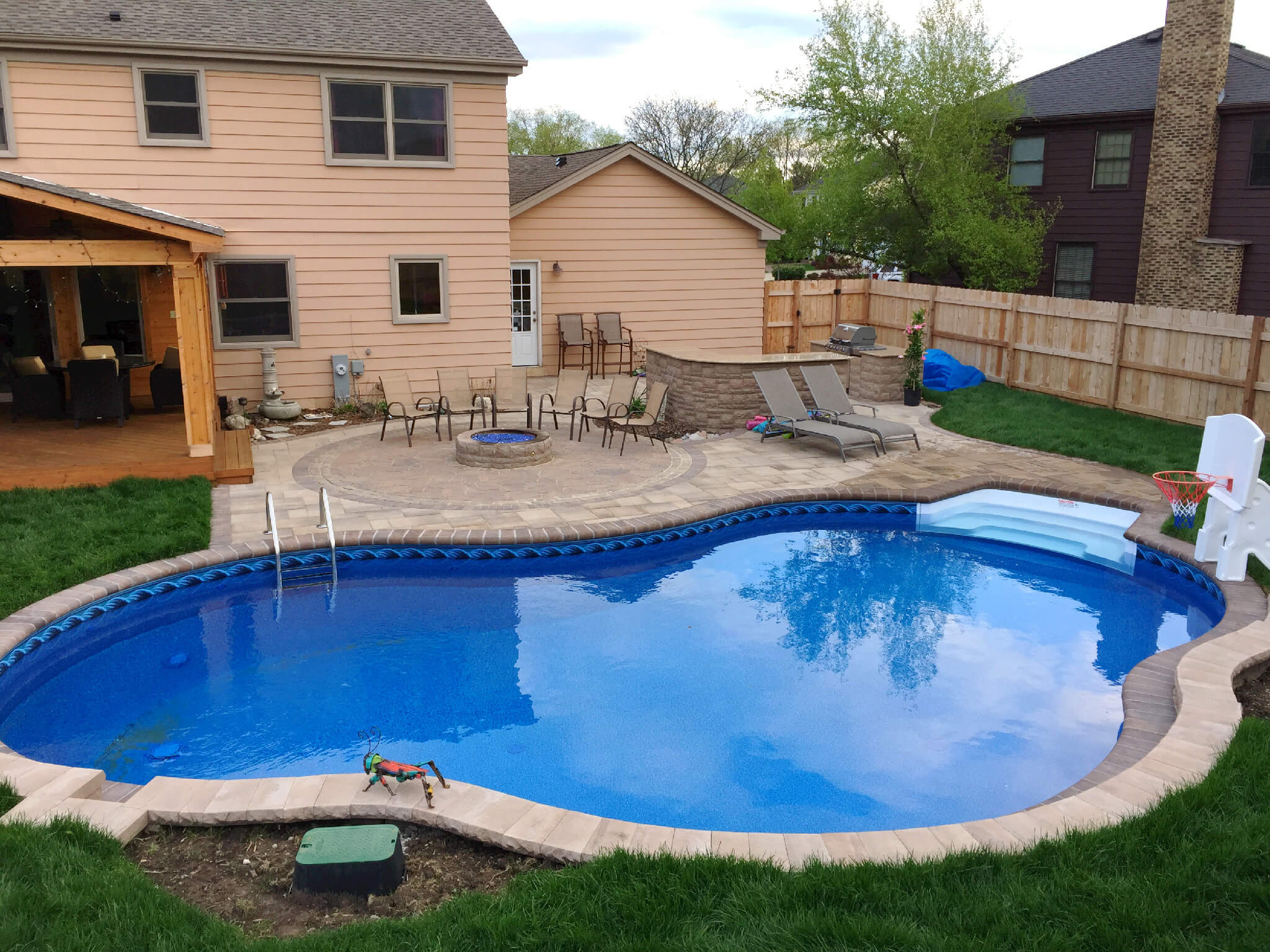 Custom patio pool deck with fire pit and outdoor kitchen