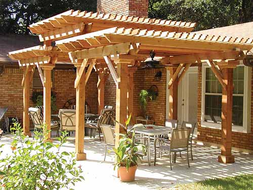 Wooden pergola off back of house with outdoor furniture