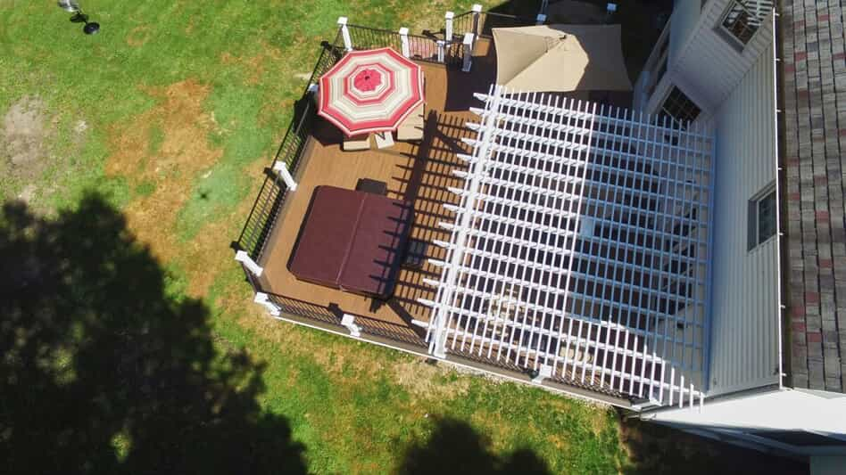 Aerial shot of backyard with pergola, umbrella & covered jacuzzi