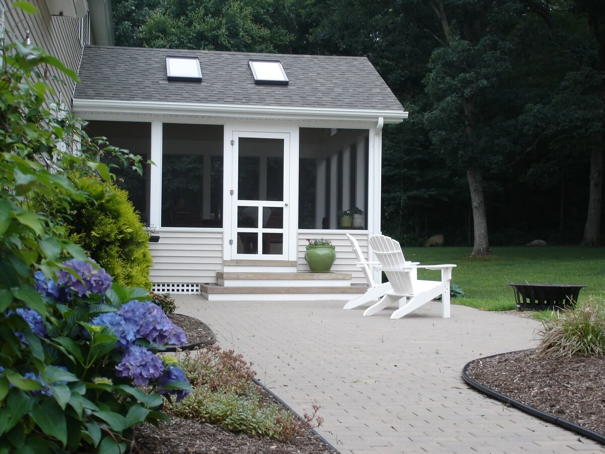 Exterior view of screened porch with outdoor lounge chairs