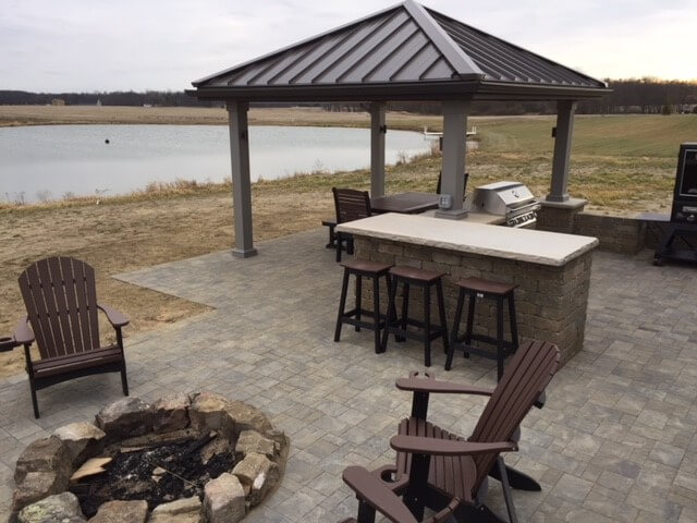 Custom patio with outdoor kitchen, bar counter and fire pit
