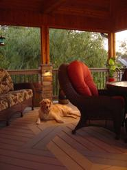 covered porch with dog and chairs