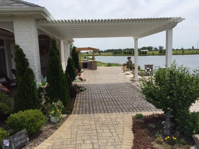 Pergola on the side of a house that is next to a lake