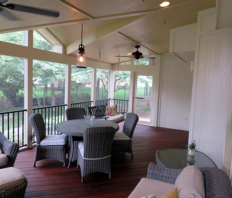 screened porch with chairs and table