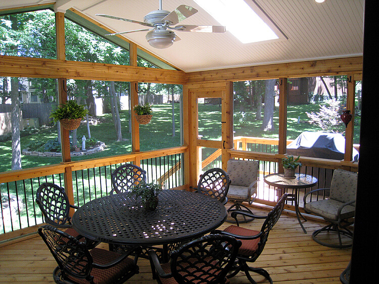 Dining area on screened porch with backyard view
