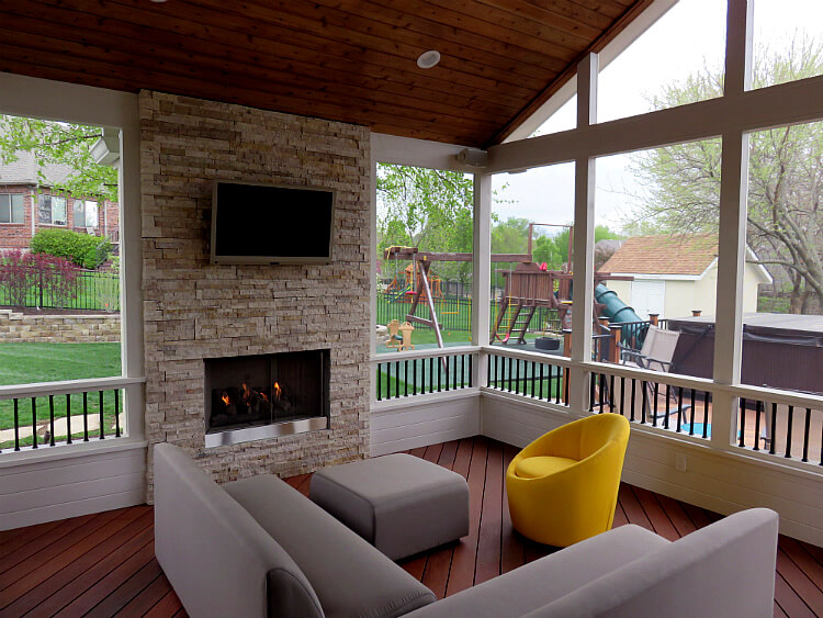 Outdoor fireplace and flat TV on custom screened porch