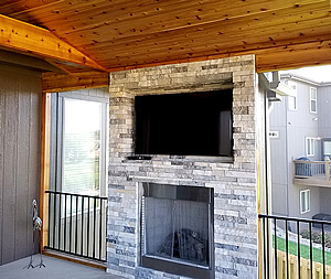 Outdoor fireplace and flat TV on screened porch
