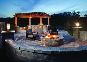 outdoor stone patio with fire feature and outdoor kitchen